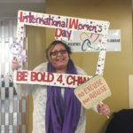 "June is standing and holding up a sign abour Internaitonal Women's Day that says ""Be Bold 4 Change"""