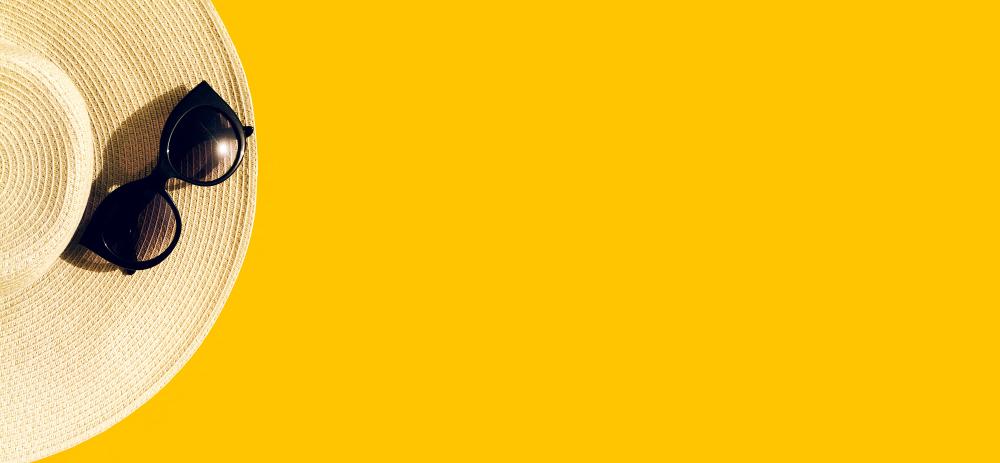 chapeau de paille et lunettes de soleil sur fond jaune